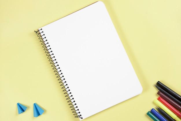 Carta piegata del mestiere e penna di pennarello vicino al blocco note a spirale in bianco su fondo giallo