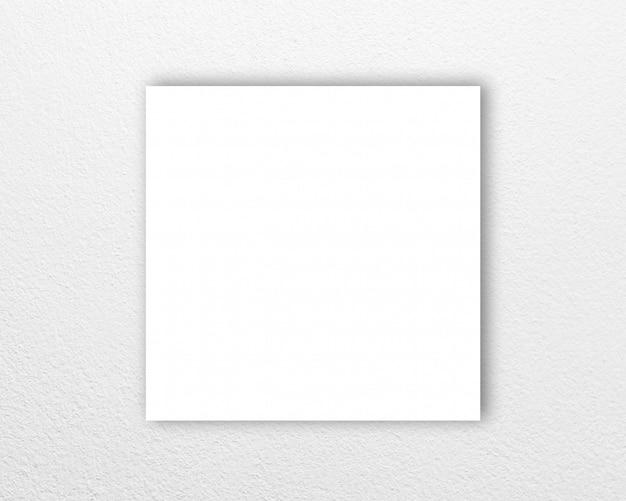 Carta quadrata nel mezzo sulla superficie del muro di cemento bianco.