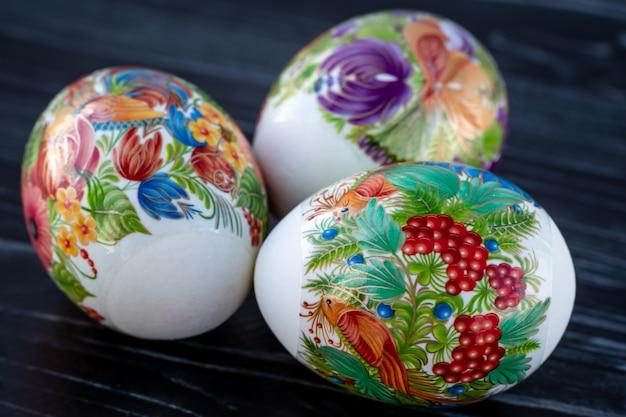 Carta regalo pasquale con uova di pasqua colorate su sfondo di legno scuro. festosa carta di buona pasqua.