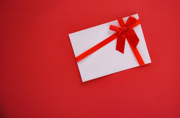 Carta regalo su sfondo rosso con fiocco di nastro rosso buono regalo sullo spazio di copia sfondo rosso vista dall'alto