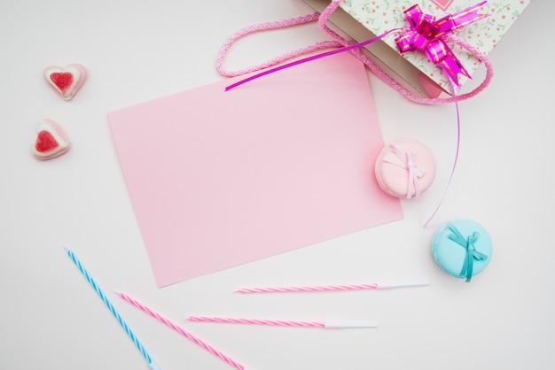 Carta rosa; macarons; candele e cuore forma caramelle e shopping bag su sfondo bianco
