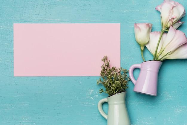 Carta rosa vuota con due vasi in ceramica su sfondo blu