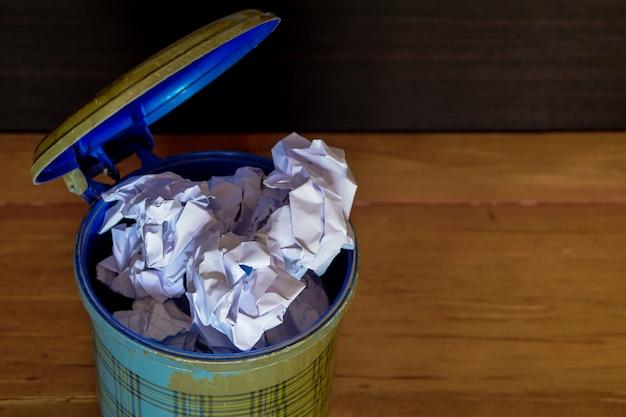 Carta sgualcita dentro e fuori dal bidone della spazzatura sul pavimento di legno.