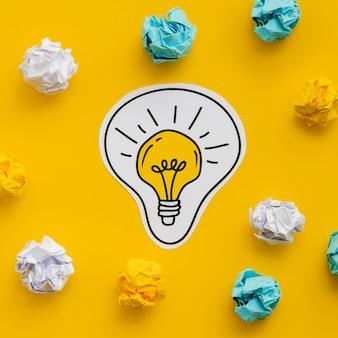 Carta sgualcita e disegno di una lampadina dorata