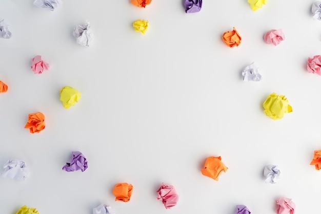 Carta sgualcita multicolore disposta in cornice circolare su sfondo bianco