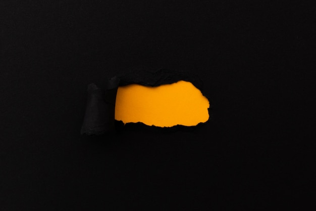 Carta strappata con uno spazio vuoto per il tuo messaggio. carta nera strappata con sfondo arancione