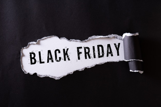 Carta strappata nera e testo black friday su bianco.