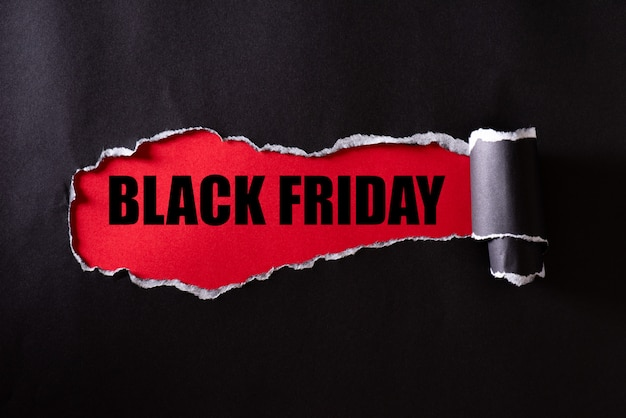 Carta strappata nera e testo black friday su rosso
