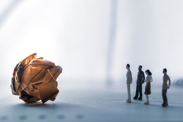Carta stropicciata con miniatura di persone in miniatura