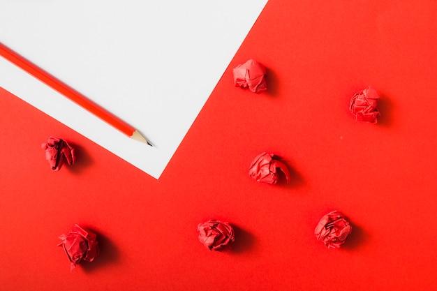 Carta stropicciata rossa su sfondo di carta doppia con matita