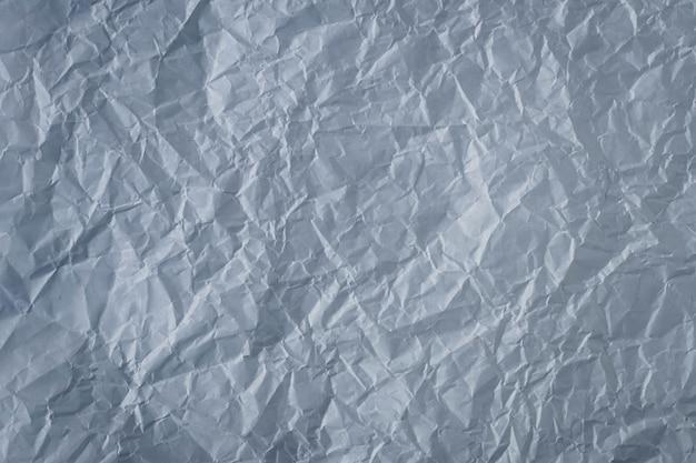 Carta stropicciata sfondo grigio. trama foglio grigio scuro.