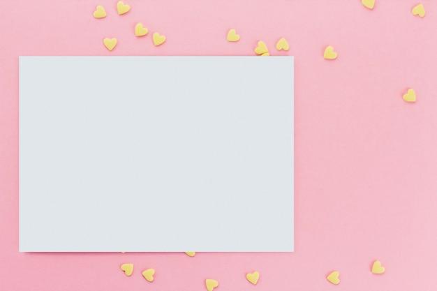 Carta su uno sfondo di confetti a forma di cuore di confetti su uno sfondo rosa copia spazio. cuori gialli