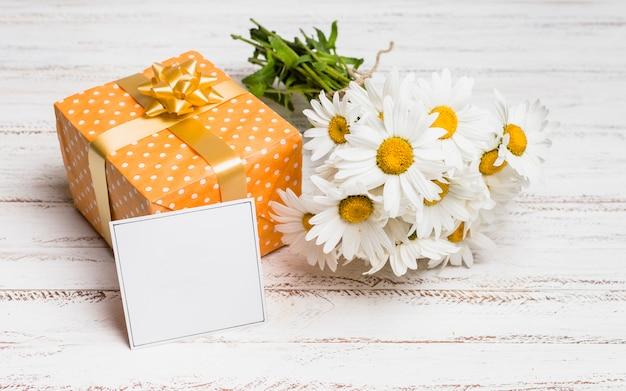 Carta vicino presente e mazzo di fiori