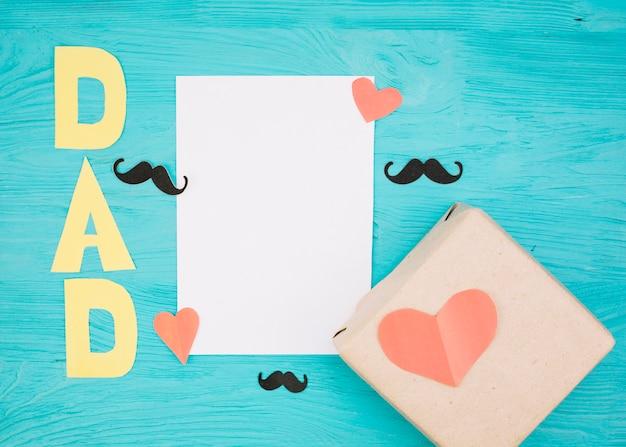 Carta vicino scatola con cuori rossi, baffi e titolo di papà