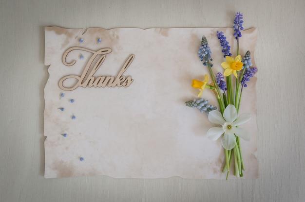 Carta vintage per il testo con grazie e bellissimo mazzo di fiori