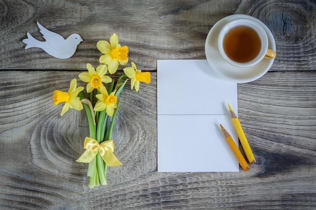 Carta vuota dell'invito con i narcisi e la tazza di tè su fondo di legno