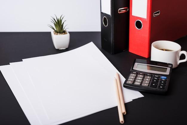 Carte bianche bianche; matite; pianta in vaso; file cartacei; tazza di caffè e calcolatrice sulla scrivania nera