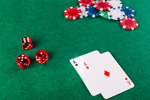 Carte da gioco dell'asso; dadi e fiches sul tavolo da poker verde