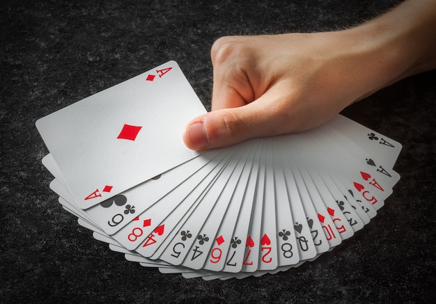 Carte da poker aperte nel ventilatore tenuto da una mano su sfondo scuro