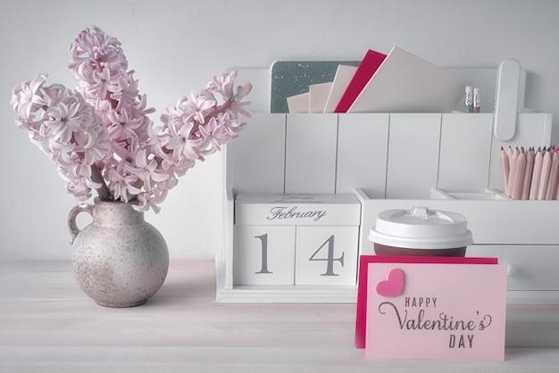 Carte di carta bianca con copia-spazio, calendario in legno, tazza di cioccolata calda e fiori di giacinto rosa
