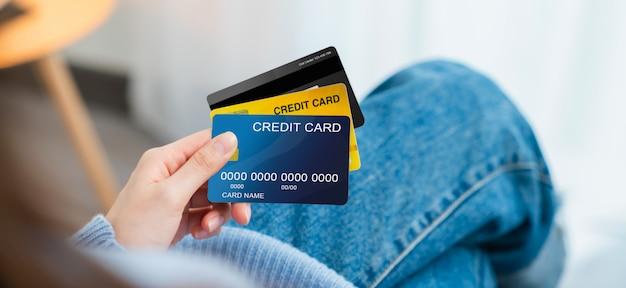 Carte di credito femminili della tenuta della mano sul sofà