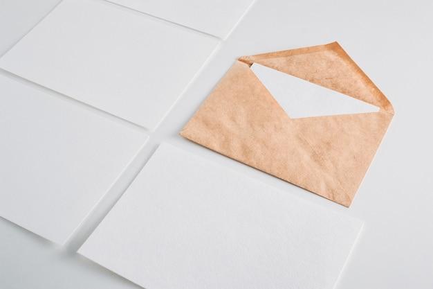 Carte di fogli vuoti del libro bianco e busta di kraft su un bianco. mockup per il design