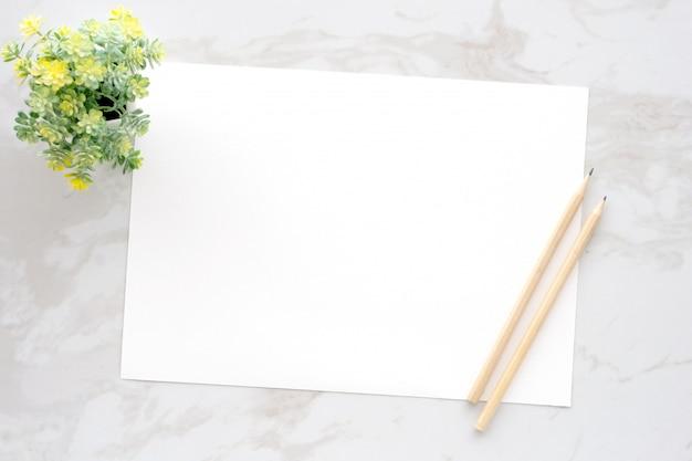 Carte e matite di nota in bianco bianche su fondo di marmo bianco
