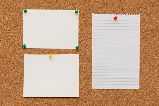Carte per appunti con puntine da disegno su scheda di sughero