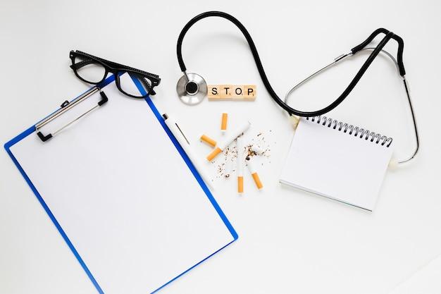 Cartella vista dall'alto con sigarette e stetoscopio