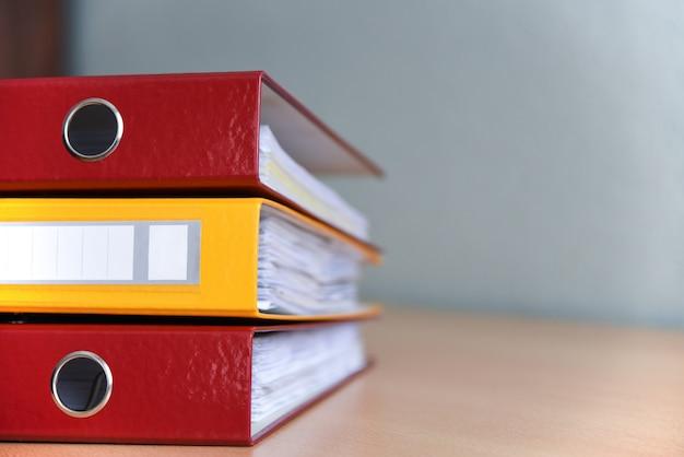 Cartelle a colori di grandi dimensioni per i documenti sul tavolo in ufficio, close-up, copia spazio