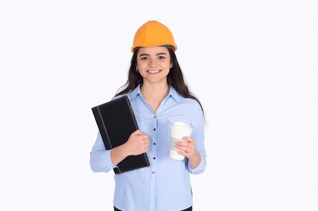 Cartelle femminili della tenuta dell'architetto con un caffè e un casco.