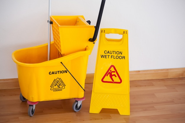 Cartello cartello giallo con secchio scopa sul pavimento contro il muro