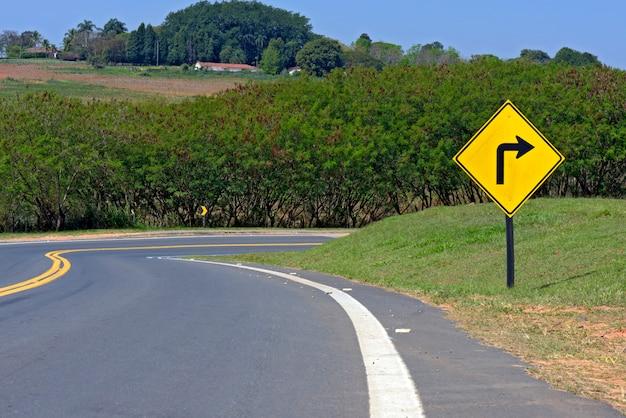 Cartello della curva a destra tagliente sulla strada