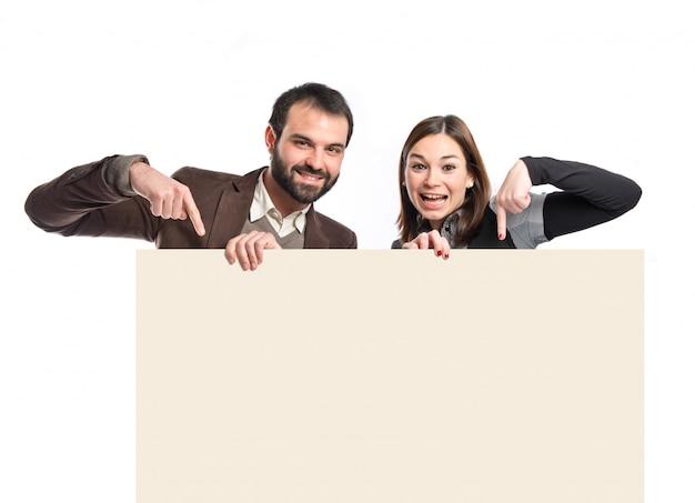 Cartello della holding delle coppie sopra priorità bassa bianca