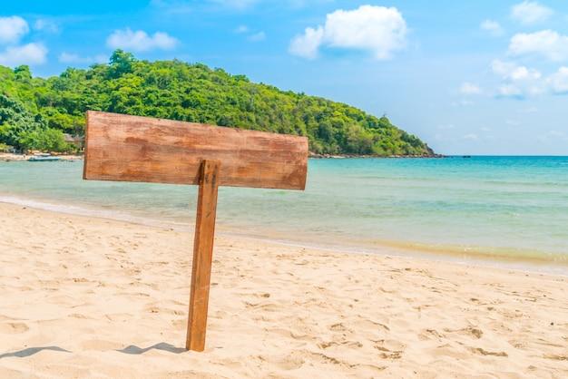 Cartello in legno sulla spiaggia tropicale