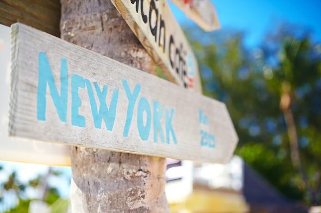 Cartello stradale tra cui di new york sul verde paesaggio tropicale