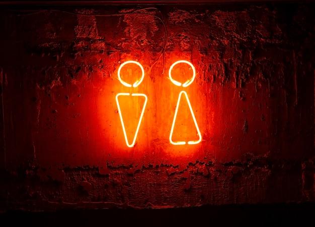 Cartello toilette al neon. segno di uomo e donna sul muro.