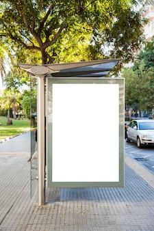 Cartellone alla fermata dell'autobus di fronte agli alberi