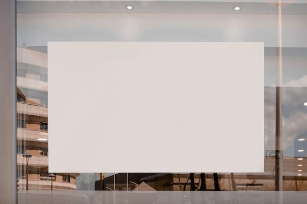 Cartellone bianco vuoto sul vetro