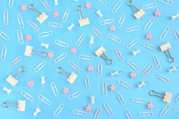 Cartoleria sparsa caoticamente. graffette bianche, bottoni clericali e piccole stelle rosa nella rivolta su azzurro. foto dall'alto.
