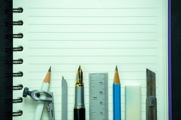 Cartoleria su quaderno. concetto di studio di architettura o ritorno a scuola. vista dall'alto e copia spazio per il testo.