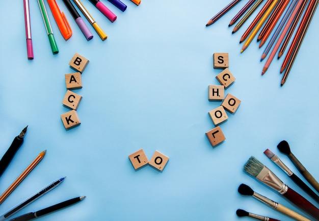 Cartoleria sulla scrivania. torna al concetto di scuola. telaio di materiale scolastico. cartoleria e lettere sul tavolo.