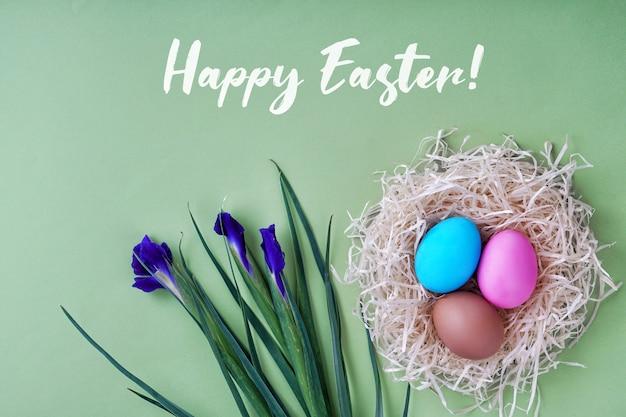 Cartolina d'auguri buona pasqua. uova colorate e nido, fiori di iris. buona idea