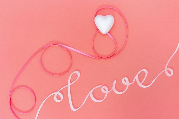 Cartolina d'auguri con cuore e nastro e parola rosa