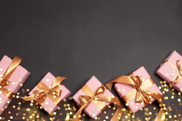 Cartolina d'auguri di buon natale e capodanno w con molti regali a sorpresa con nastri di atlante d'oro su sfondo scuro
