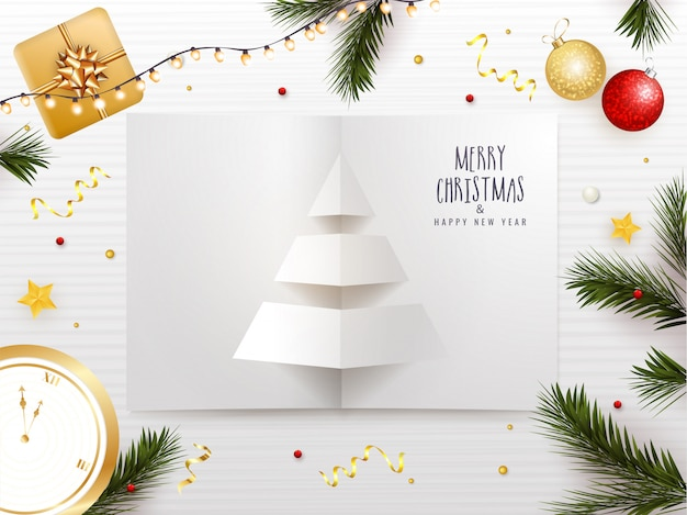 Cartolina d'auguri di buon natale e felice anno nuovo con carta tagliata albero di natale, palline, scatola regalo, orologio e foglie di pino decorate su strisce bianche