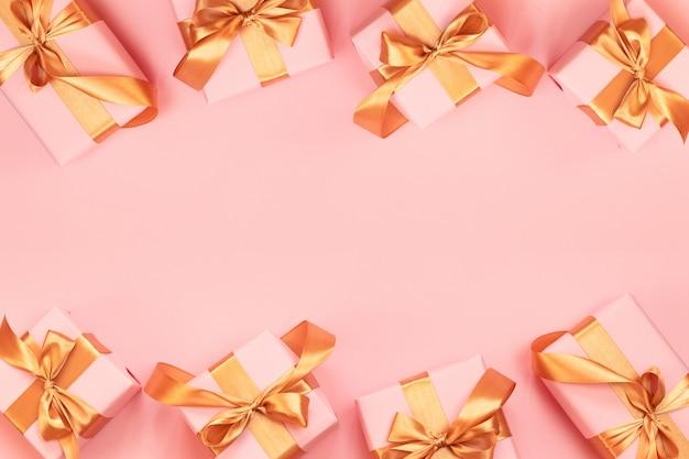 Cartolina d'auguri di buon natale e felice anno nuovo con scatola regalo di carta, fiocco in nastro d'oro su uno sfondo rosa