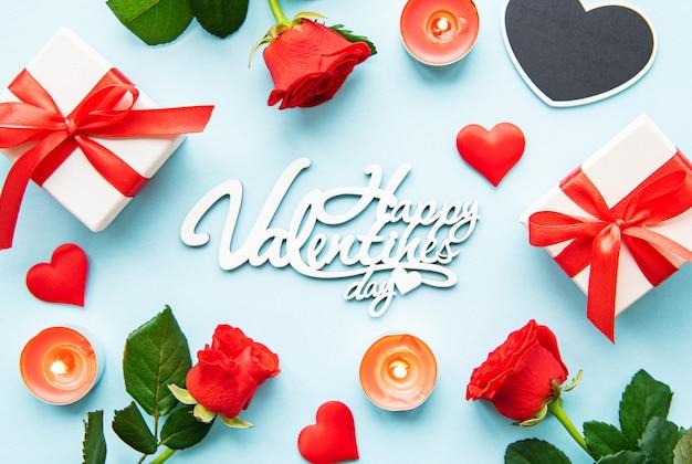 Cartolina d'auguri di felice giorno di san valentino con regalo, rosa rossa, candele e cuori