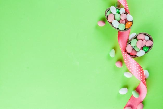 Cartolina d'auguri di festa di pasqua, con coniglietto di pasqua al cioccolato, uova di caramella, uova di quaglia e nastro festivo, vista dall'alto