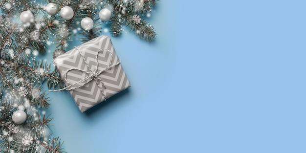 Cartolina d'auguri di natale con i rami dell'abete, contenitore di regalo bianco, fiocchi di neve sull'azzurro.